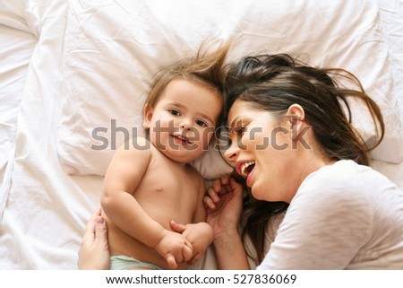 Baby girl and mother lying in bed. Space for copy.