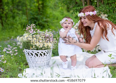 Baby girl and mother outdoors portrait. Sunny summer day Family Picnic. Happy family concept. Portrait of beautiful angel girl playing outside
