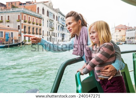 Baby girl and mother poiting while travel by vaporetto in venice, italy - stock photo