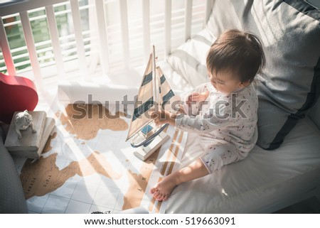 baby girl at home dreaming of travel and tourism, exploring the world map and wooden sailboat. Go on an adventure! Cute child girl with vintage sailboat on white bed and world maps.