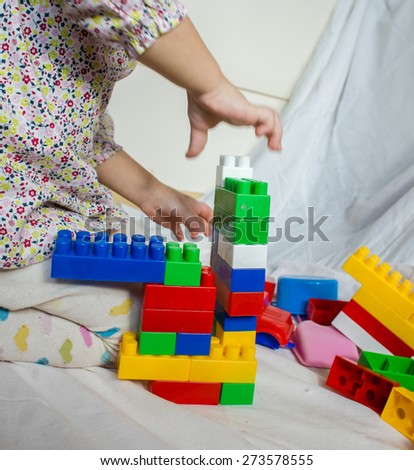baby girl at homeplaying with constructor - stock photo