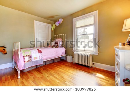 Baby girl bedroom interior with pink bed and hardwood floor. - stock photo