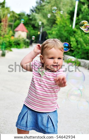 baby girl catching soap bubbles in the park