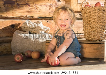 Baby Girl Caucasian One Year Old Sitting and Smiling near Wooden Barn or House with Sack, Box and Basket with Apples on Background, Golden sunset light, holds apple in hand