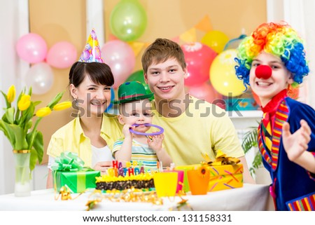 baby girl celebrating first birthday with parents and clown - stock photo