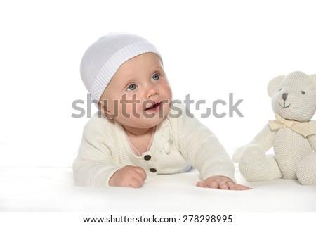 baby girl child lying down on white blanket smiling happy white  hat warm cloting fashion portrait face studio shot isolated on white caucasian teddy bear - stock photo