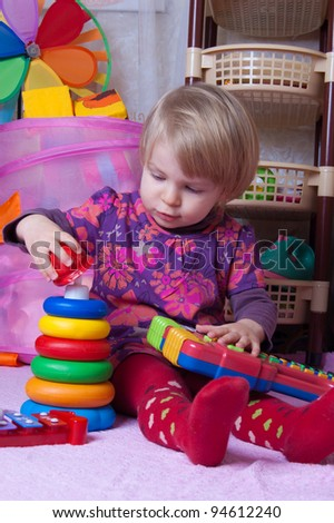 Baby girl collecting pyramid in playing-room - stock photo