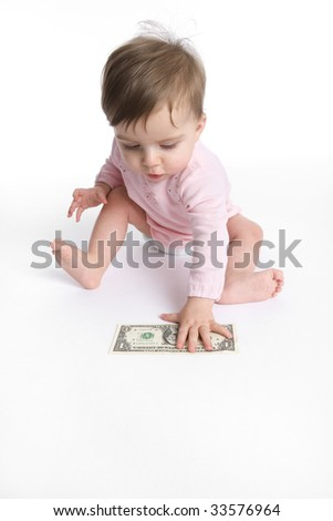 Baby girl collects a dollar from the floor - stock photo