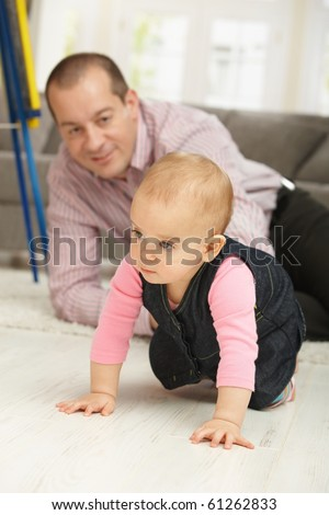 Baby girl crawling on floor, dad watching in background smiling.?
