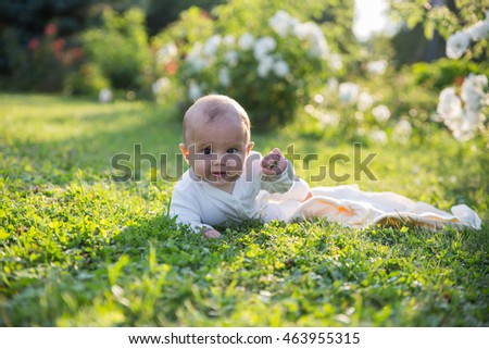 Baby girl crawling on the grass with white flowers. Selective focus on her eyes.