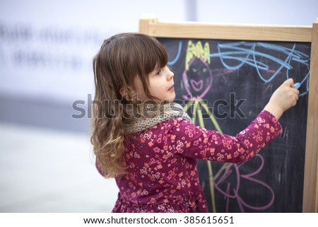 baby girl draws a chalk on a blackboard in the children's area of the shopping center, the concept of the family shopping, children's stores