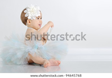 Baby girl dressed in white tutu and wearing big flower headband - stock photo