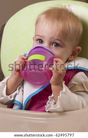 Baby girl drinking from her little sipper cup - stock photo