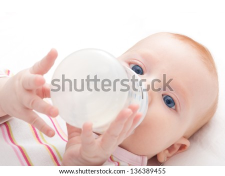 Baby Girl Drinking Milk from Bottle on White Background - Shallow Depth of Field