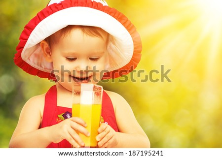 baby girl drinking orange juice in the summer - stock photo