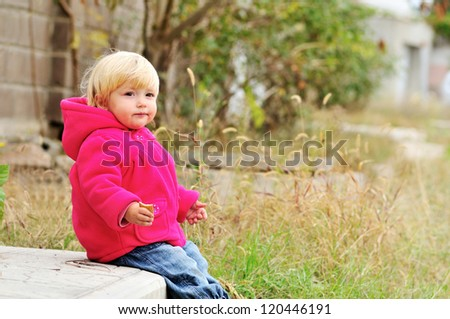 baby girl eating cake and sitting on the threshold - stock photo