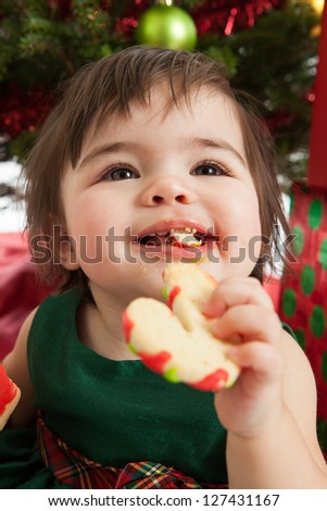 Baby girl eating Christmas cookies under a Christmas tree