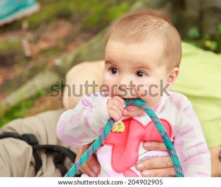 Baby girl eating climbing rope outdoor  - stock photo