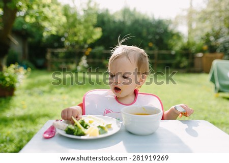 Baby girl eating her lunch in the garden outside in summer
