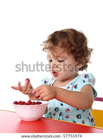 Baby girl eating raspberry - stock photo