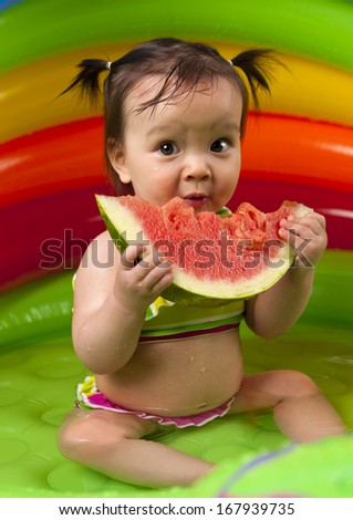 Baby girl eating watermelon in wading pool - stock photo
