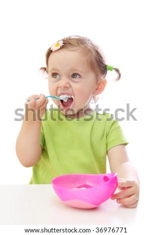 Baby girl eating yoghurt isolated on white background - stock photo