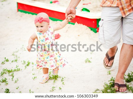 baby girl first steps holding her father hand - stock photo