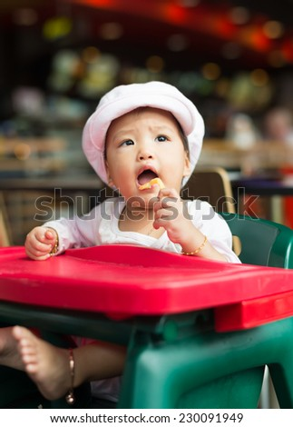 baby girl have lunch at fast food restaurant - stock photo