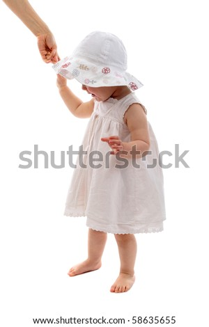 baby girl having her first step as her mums holding her hand - stock photo