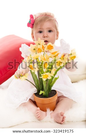 Baby girl holding daffodils in a pot  and sitting on fluffy blanket - stock photo