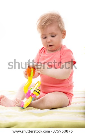Baby girl holding flower toy and playing on blanket home - stock photo