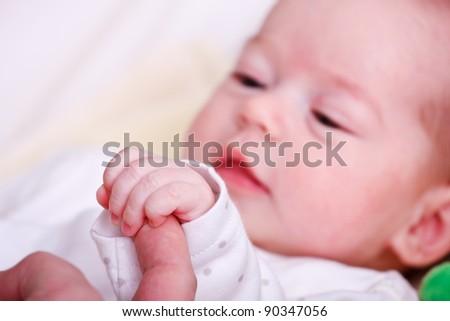 Baby girl holding her mother's finger - stock photo