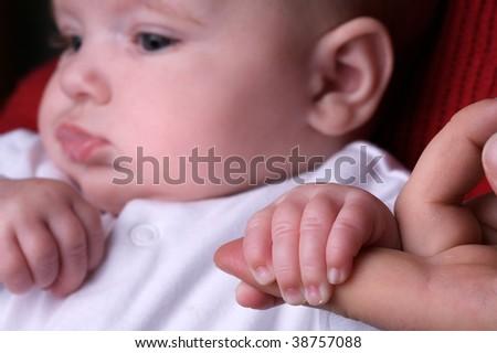 Baby girl holding mum's finger - stock photo