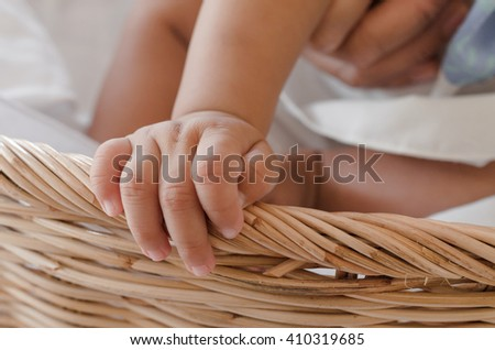 Baby girl in a basket. Selective focus on hand. - stock photo