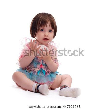 baby girl in a colorful dress isolated on a white background playing with a white ball  - stock photo