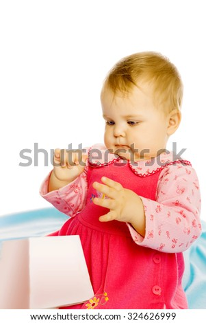baby girl in a dress sitting and holding a box