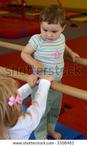 Baby girl in a gym is looking down on another toddler.