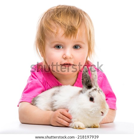 baby girl in a pink T-shirt with her small white rabbit close-up - stock photo