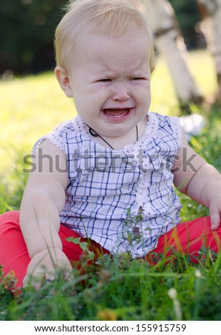 baby girl in a plaid shirt sitting on the grass and crying out loud - stock photo