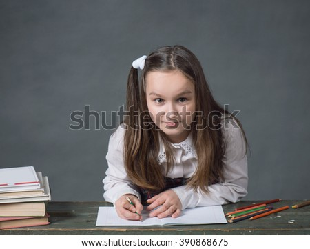 Baby girl in a school uniform sitting at a table with books and doing homework - stock photo