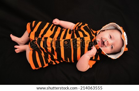 Baby girl in a tiger print outfit against plain background - stock photo