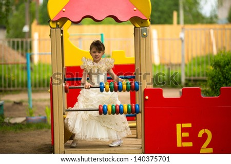 Baby girl in an elegant dress on the playground