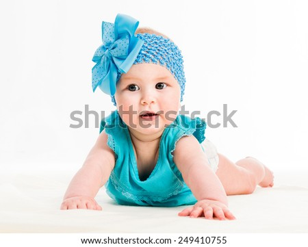 baby girl in blue decoration on the head and dress on white background - stock photo
