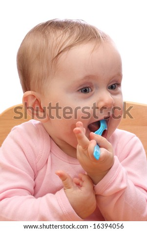 Baby girl in chair with a spoon - stock photo