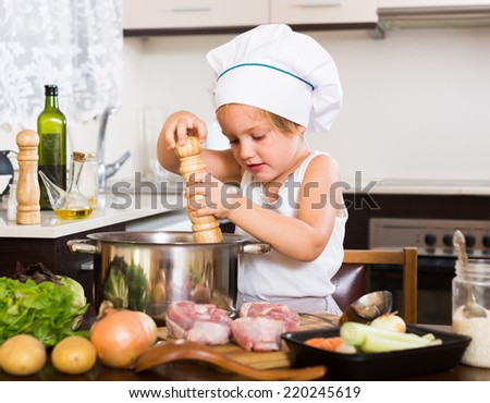 Baby girl in chef�¢??s hat cooking with meat and vegetables at home kitchen  - stock photo
