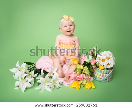 Baby girl in Easter outfit with Easter Eggs, and tulip flowers, sitting on blanket - stock photo
