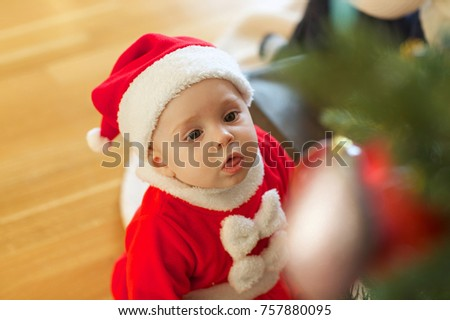 Baby girl in front of Christmas tree at home