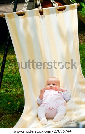 Baby girl in lying in the striped hammock on a summer day - stock photo