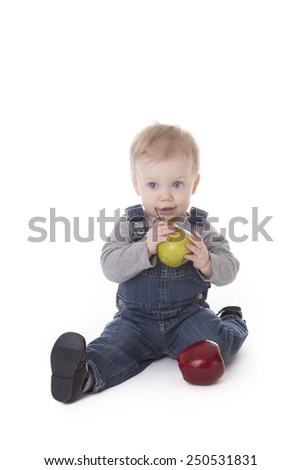 Baby girl in overalls choosing between apple or pear isolated on white - stock photo