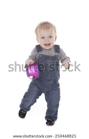 Baby girl in overalls holding purple cup and walking isolated on white